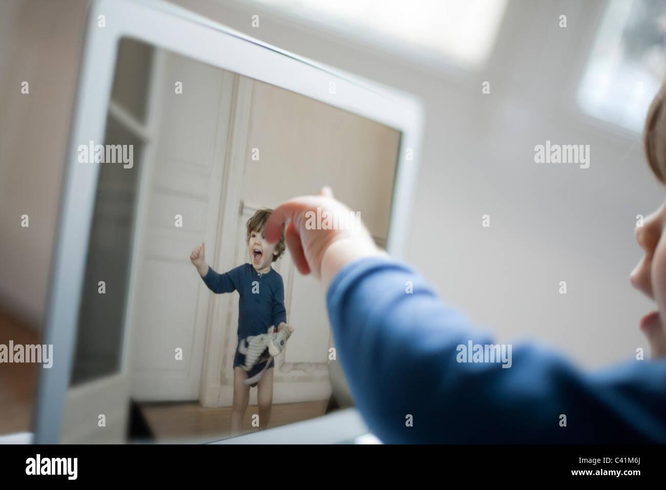 Toddler pointing at laptop screen - Stock Image