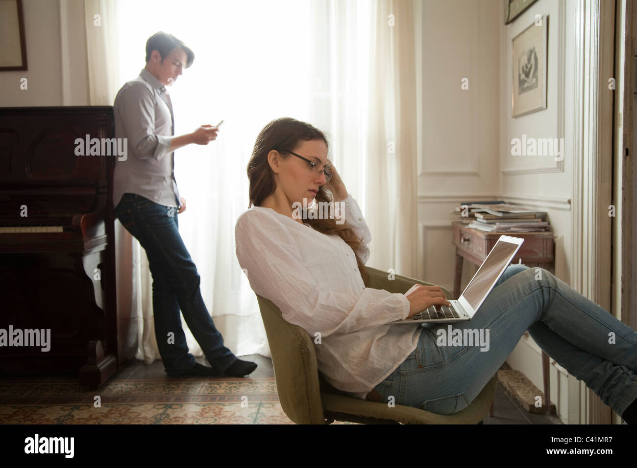 Woman using laptop computer at home, man holding cell phone in background - Stock Image