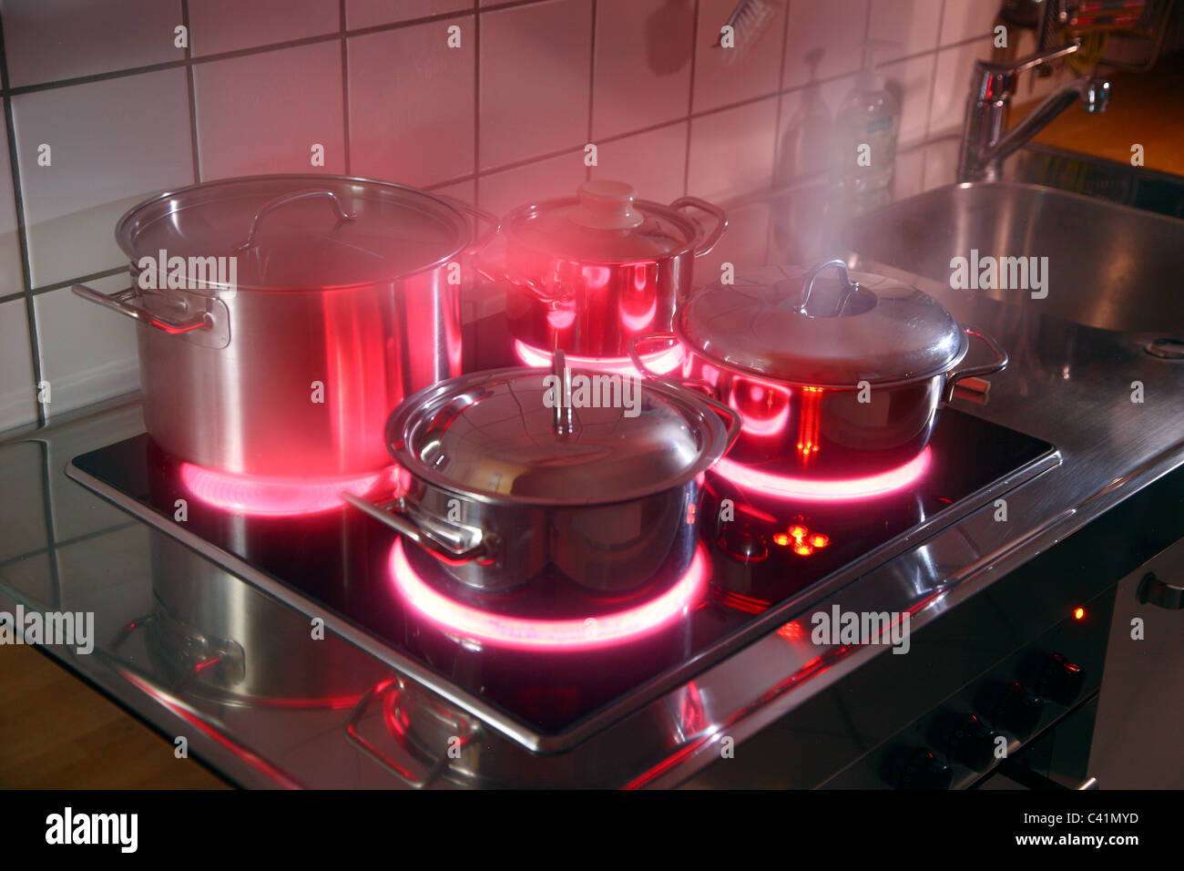 home kitchen, cooking pots, made of stainless steel, on a hot glass-ceramic cooking ring. red, hot glowing. - Stock Image