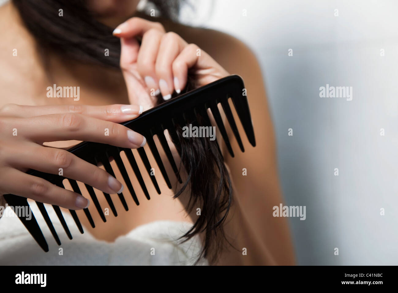 Woman combing her hair, cropped - Stock Image