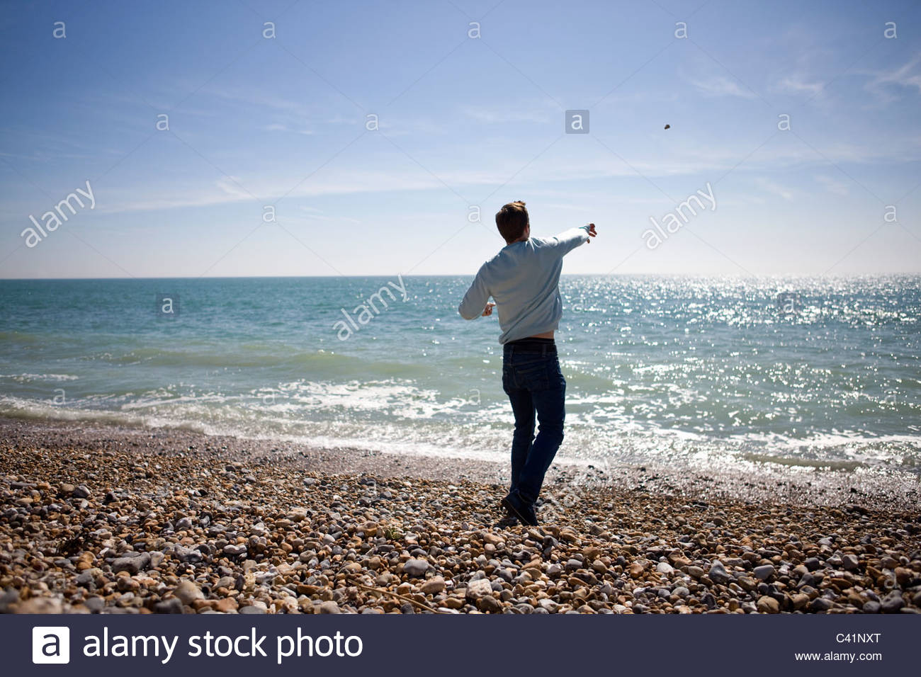 Hand Throwing Stone : A young man throwing stones in the sea stock photo