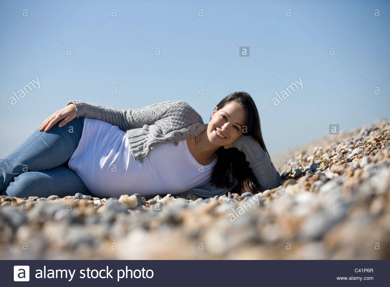 A pregnant woman lying on the beach, smiling - Stock Image