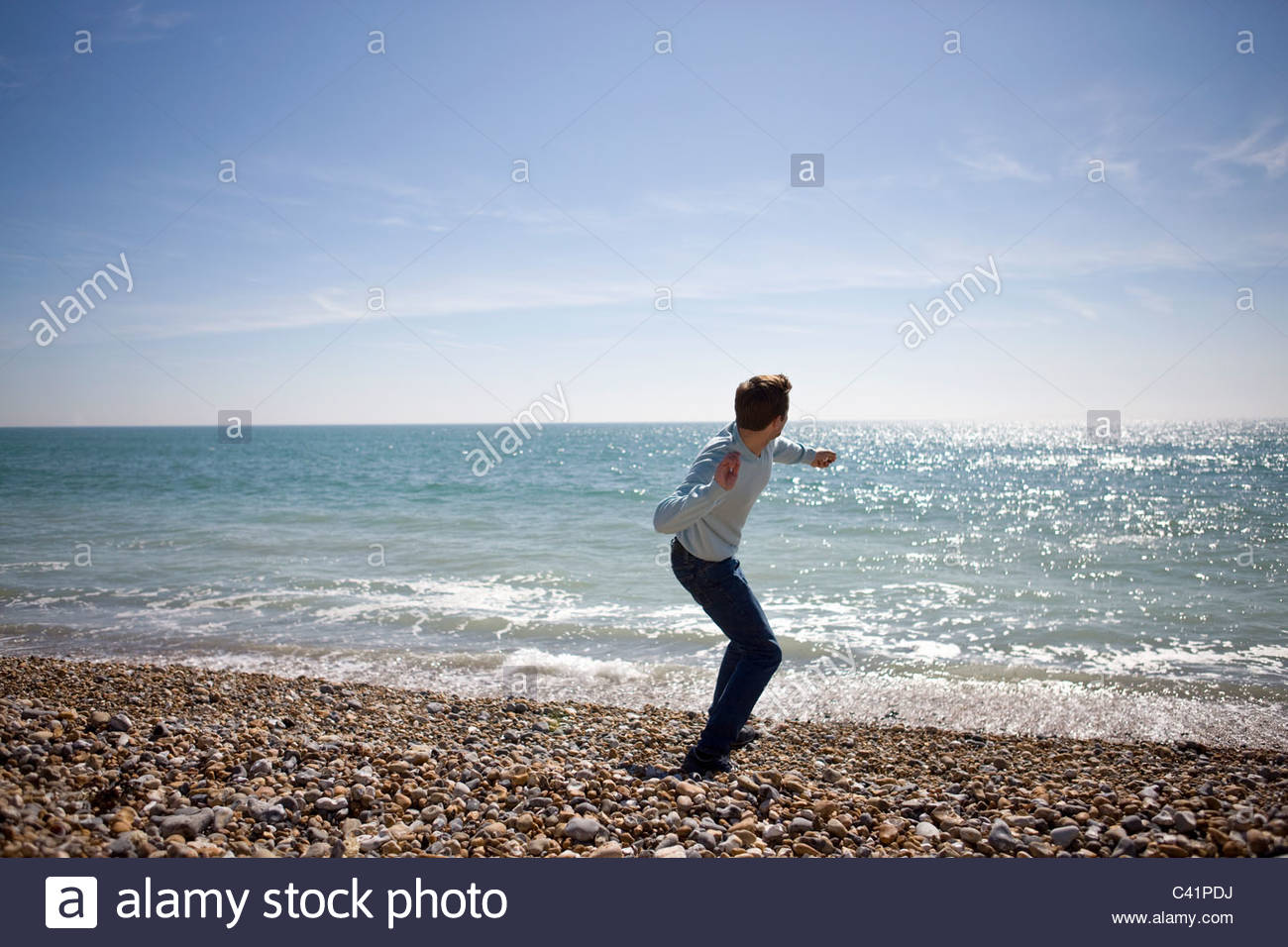 A young man throwing stones in the sea - Stock Image