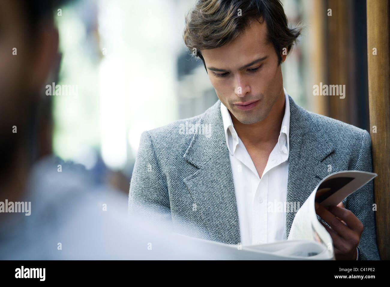 Man leaning against wall reading newspaper - Stock Image