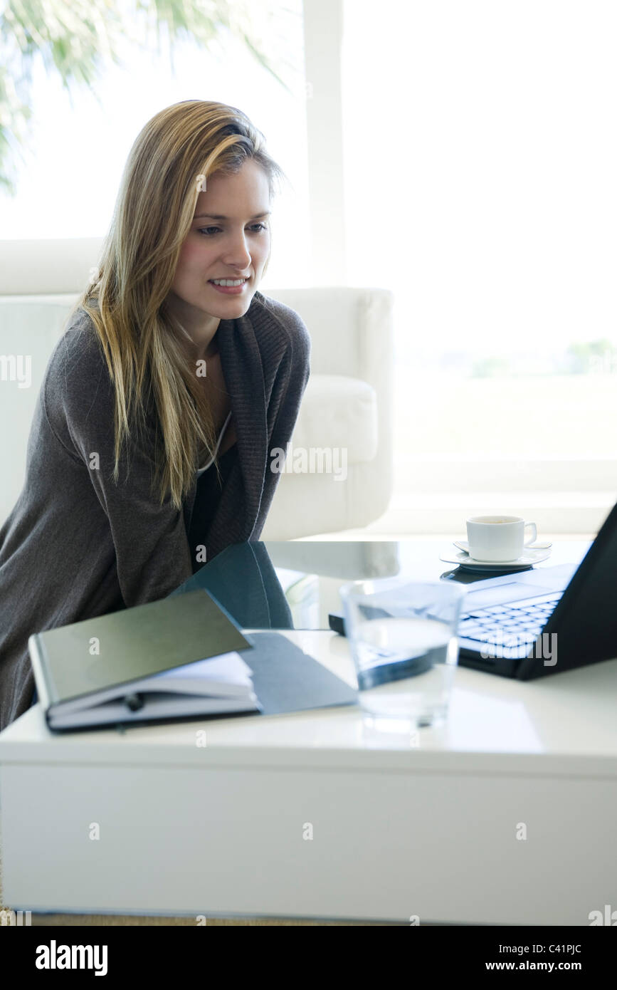 Woman using laptop computer at coffee table Stock Photo