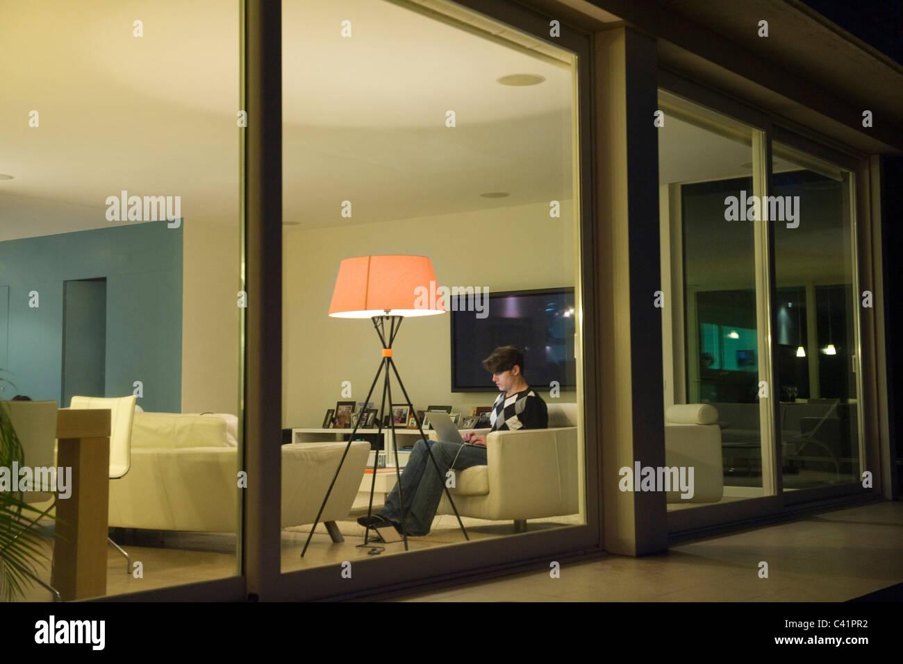 Man using laptop in living room, viewed through window - Stock Image
