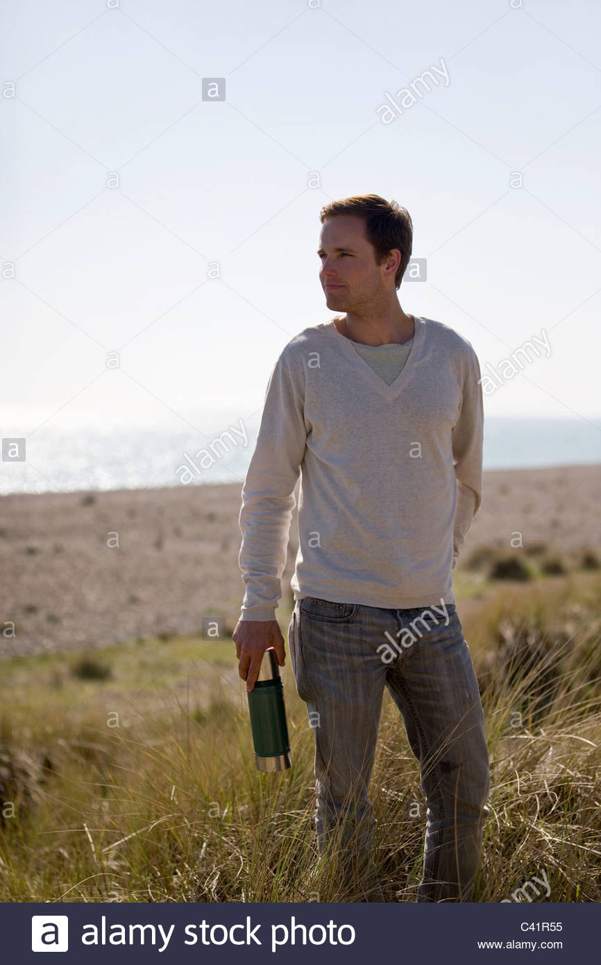 A young man walking amongst the sand dunes, holding a flask - Stock Image