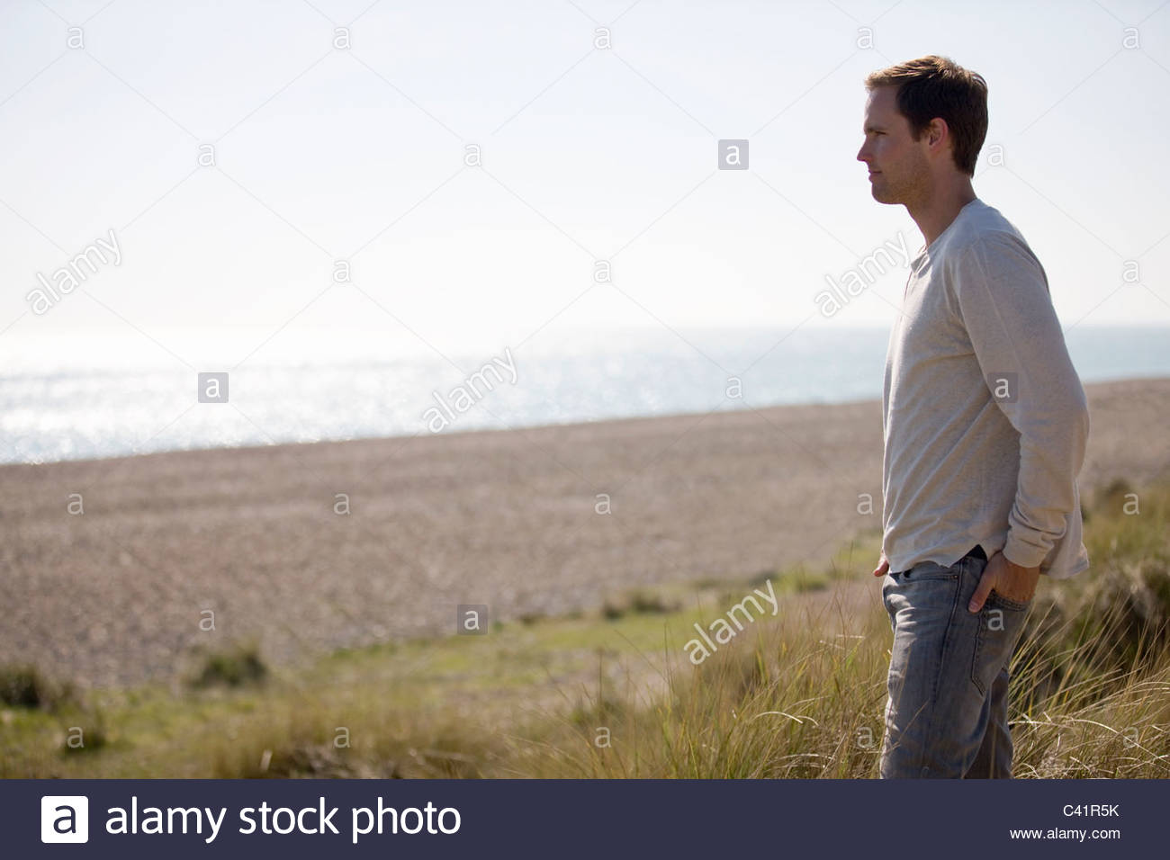 A young man standing amongst the sand dunes, looking out to sea - Stock Image