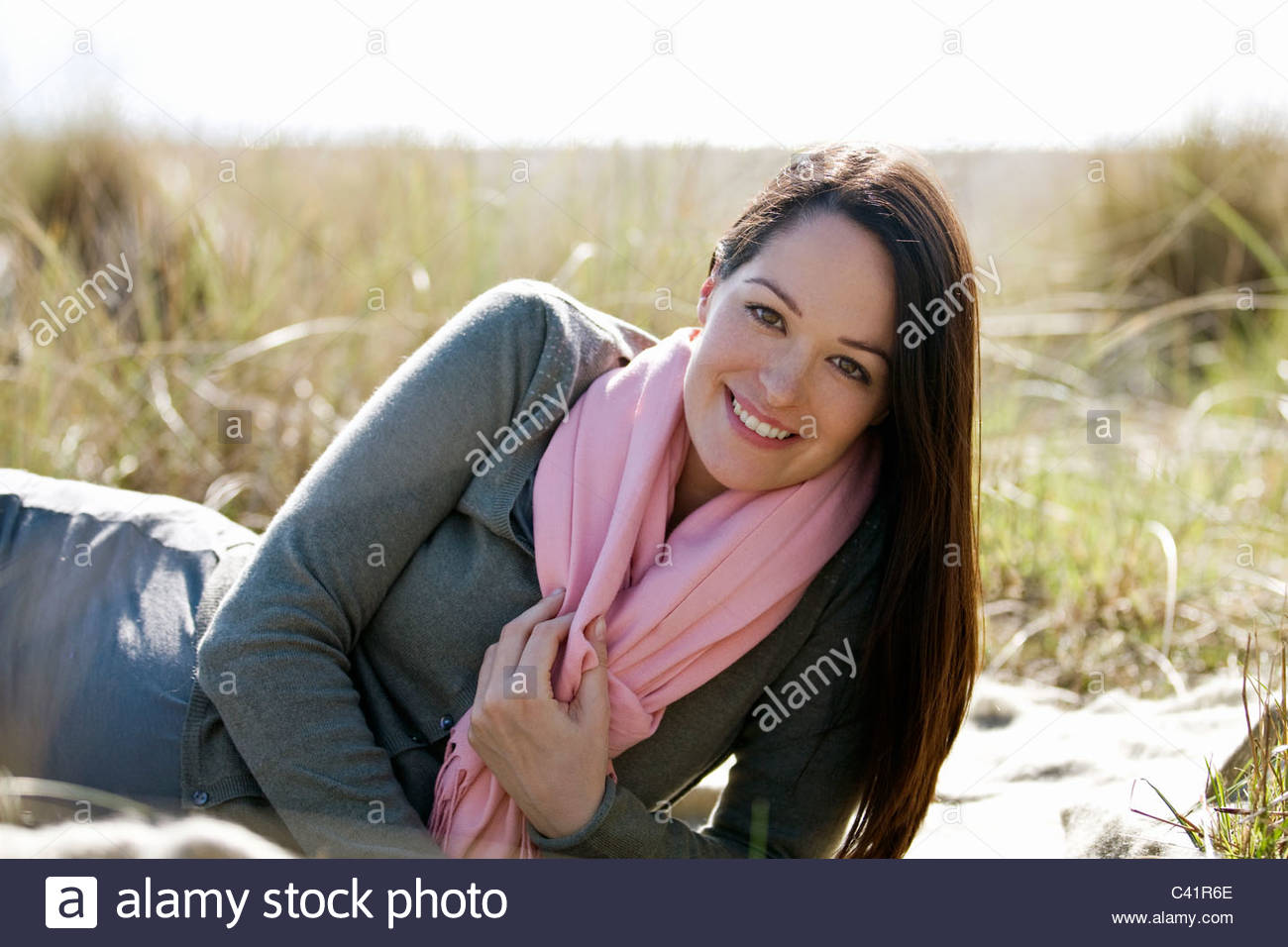 A pregnant woman lying amongst long grass, smiling - Stock Image