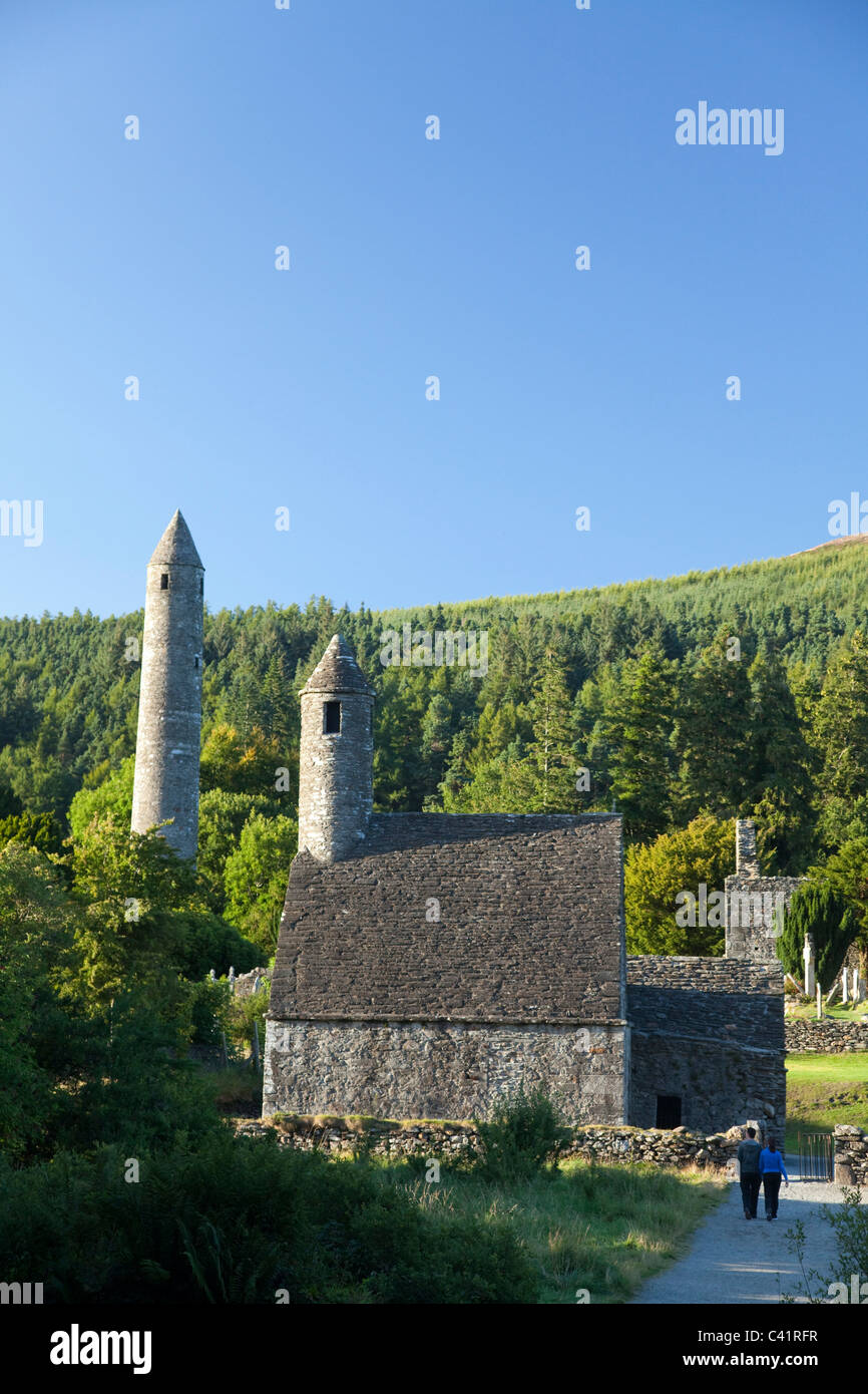 Visitors beneath St Kevin's church and round tower, Glendalough monastic site, County Wicklow, Ireland. - Stock Image
