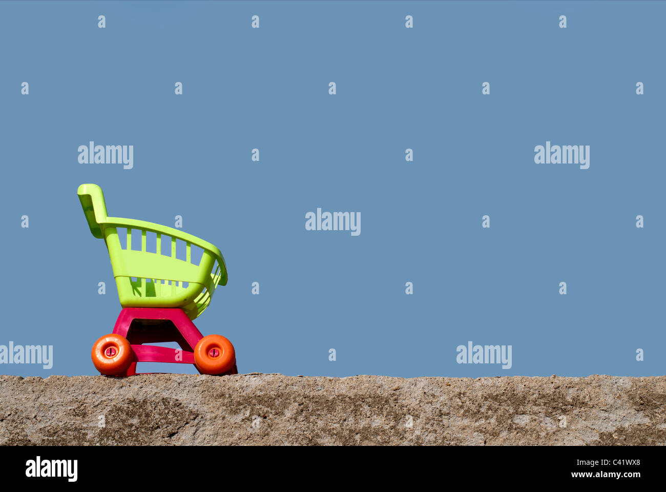 shopping trolley sitting on a rock wall,on a blue sky,shopping cart,shopping buggy,blue sky - Stock Image