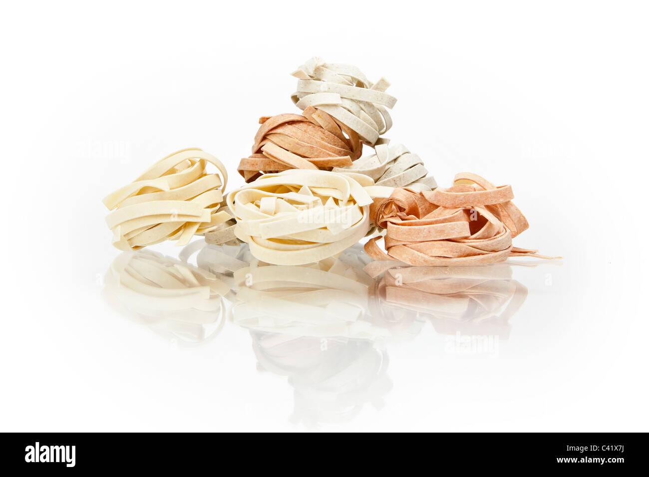 Tagliatelle pasta in three colors on white background - Stock Image