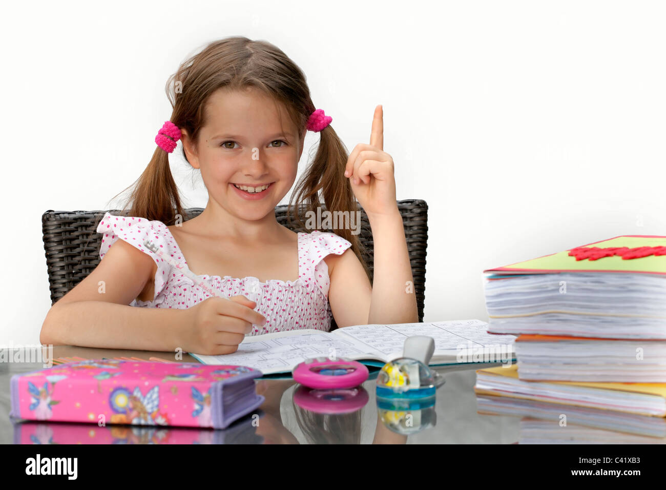 7 year old girl at the table with homework - Stock Image