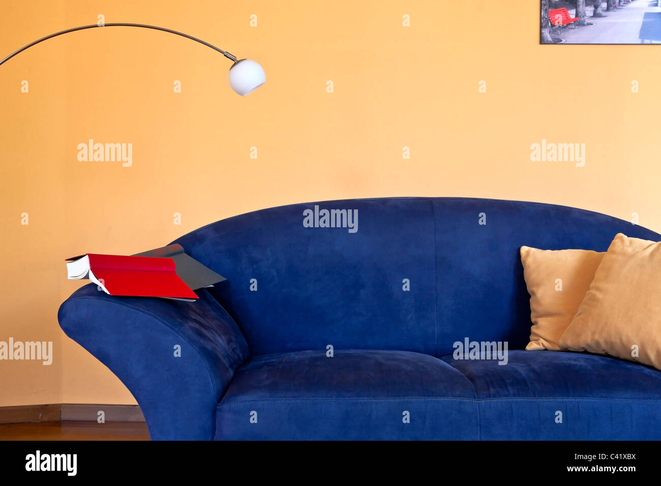 a reading corner with a blue couch, a book and a reading lamp - Stock Image