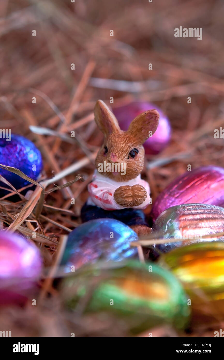 an Easter bunny with Easter eggs in a nest of straw - Stock Image