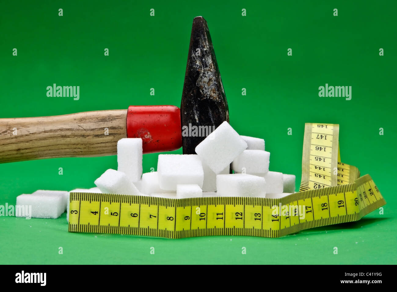 a hammer which is disturbing sugar cubes for a healthier nutrition in the future - Stock Image