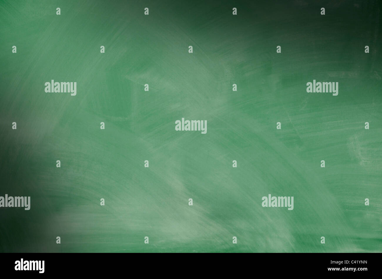 Green chalkboard with smeared chalk eraser marks lit diagonally - Stock Image