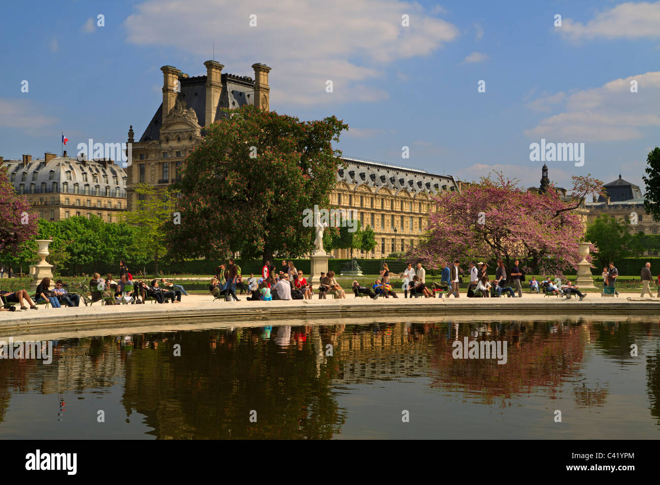 Tourists and Parisians relax in spring sun around one of the fountain pools in the Jardins de Tuileries - Stock Image