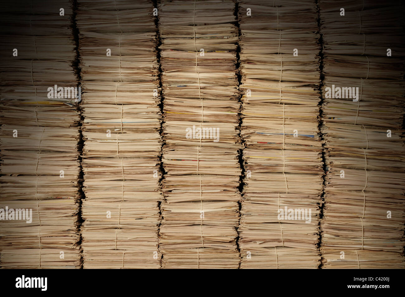 Five uniform piles of newspapers to be recycled lit from above - Stock Image