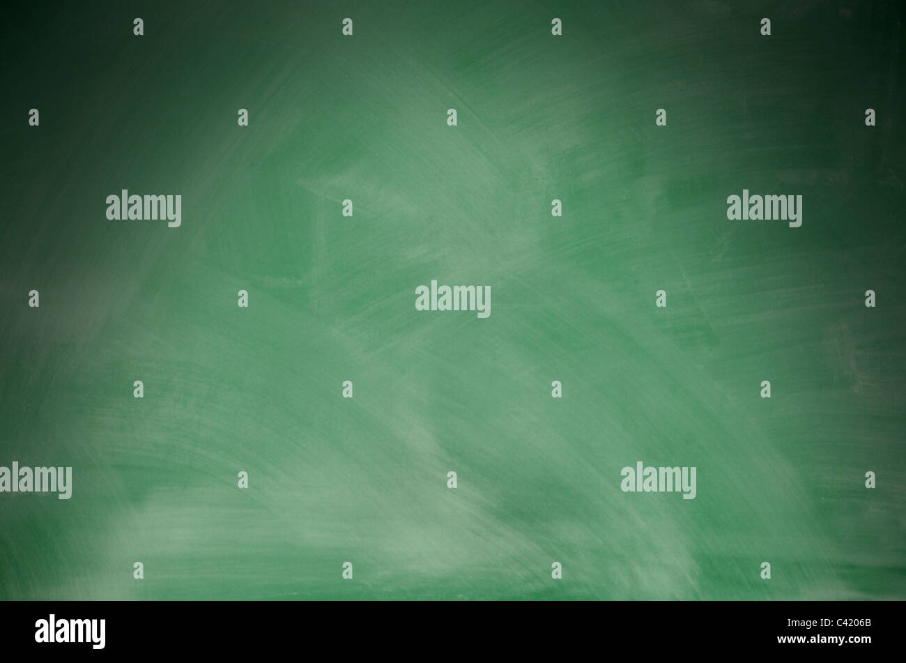 Green chalkboard with eraser marks lit dramatically from above - Stock Image