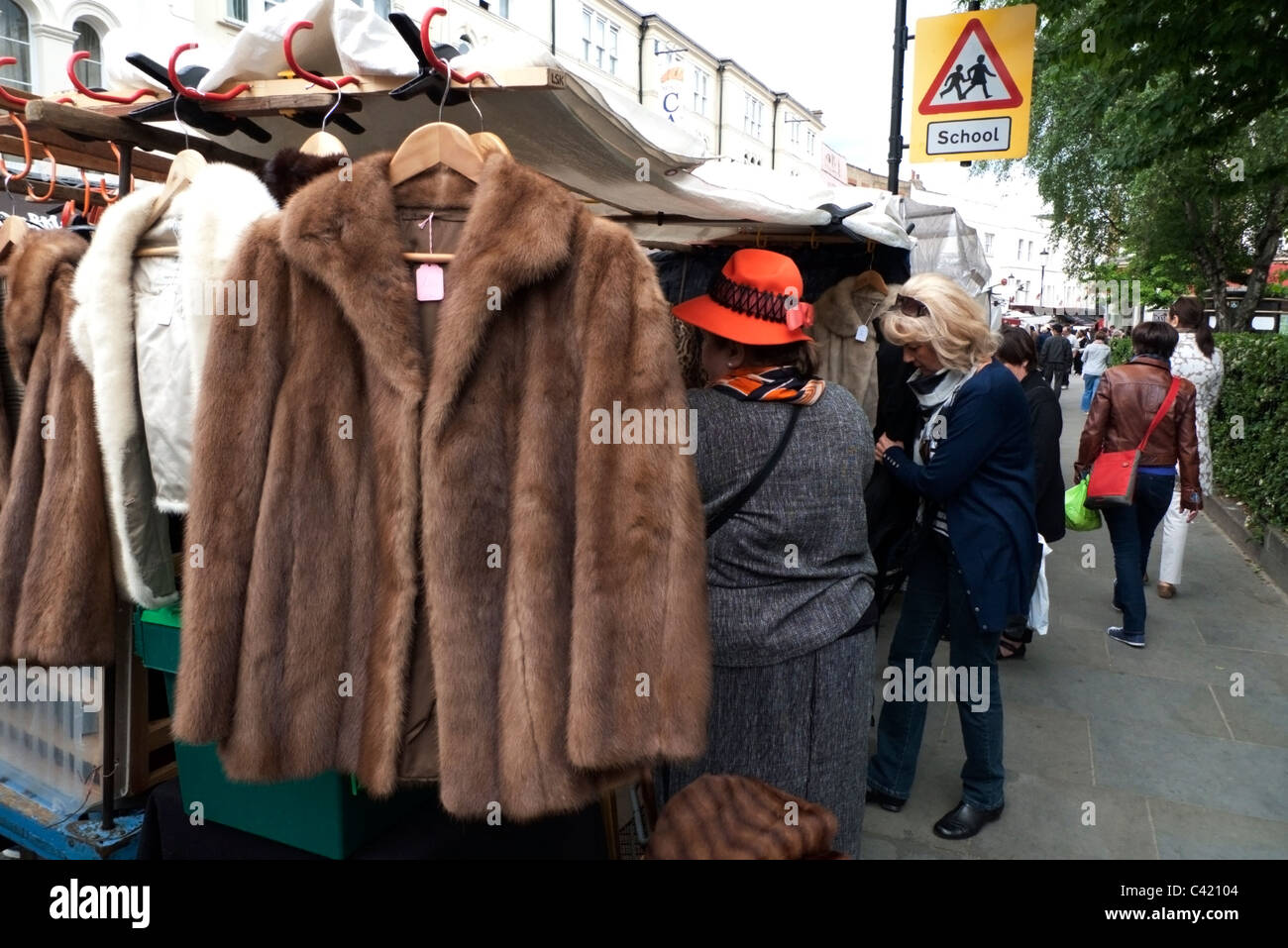 A Woman Shopping And Market Trader On A Vintage Fur Coat Jacket For Sale On A Portobello Road Antique Clothing Market Stall In Notting Hill London England