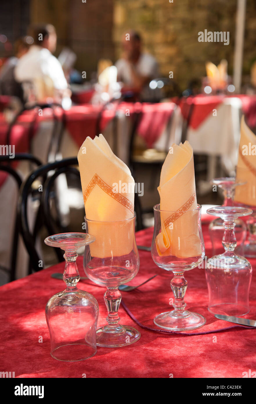 Glasses with napkins in table setting with people in background of restaurant Sarlat-la-Caneda Dordogne France - Stock Image