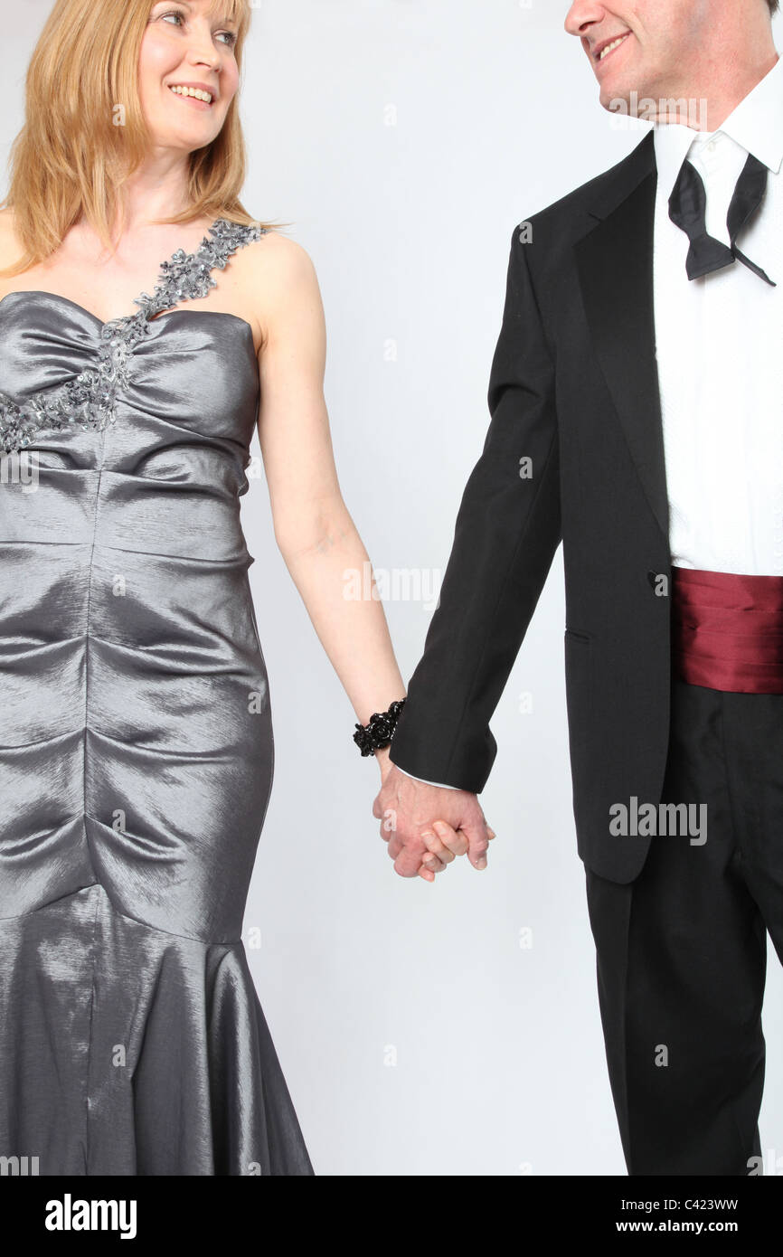 Couple wearing evening wear hold hands - Stock Image