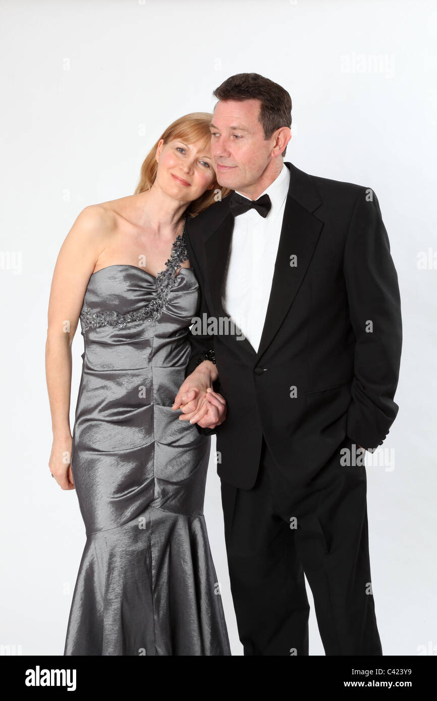Couple wearing formal clothes walk arm in arm - Stock Image