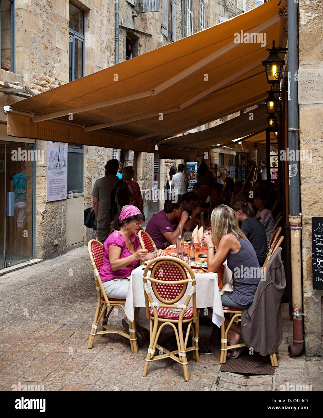 People eating at tables under awning Sarlat-la-Caneda Dordogne France - Stock Image