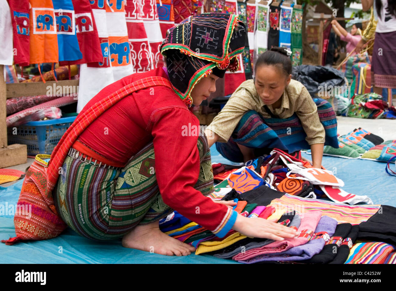 Ethnic Hmong hill tribe women are selling goods at a street market in communist Laos. - Stock Image