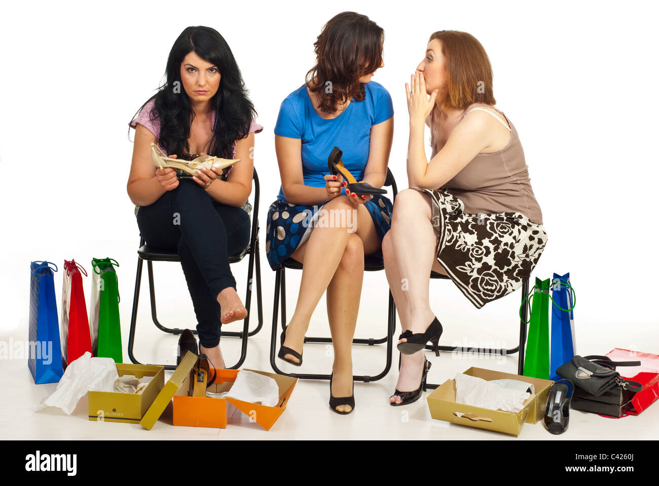 Two women gossip or telling secrets about their friend with sad face in a shop place at shopping - Stock Image