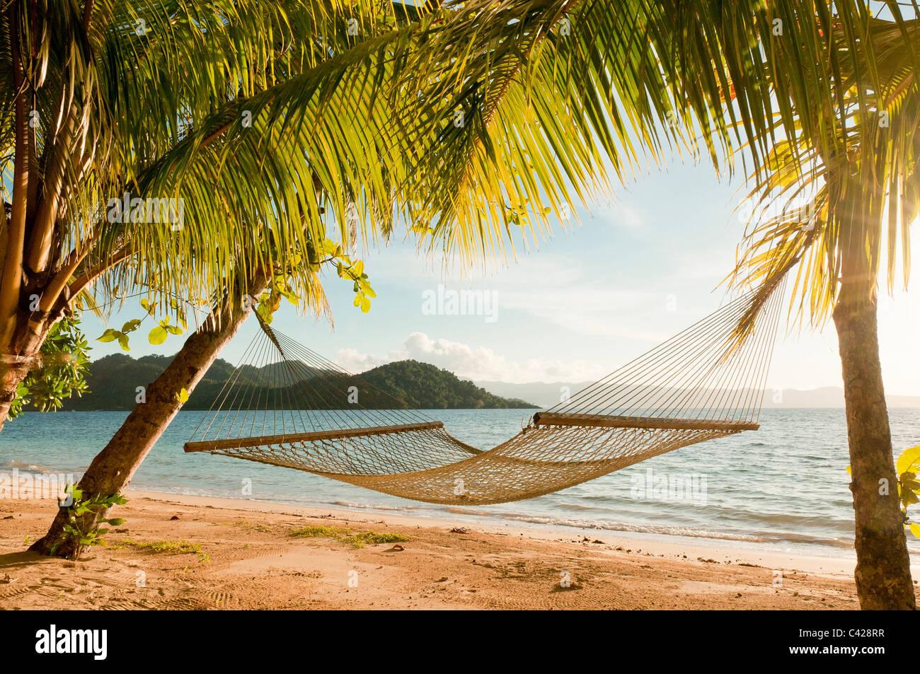 Hammock on beach at Matangi Private Island Resort, Fiji. - Stock Image