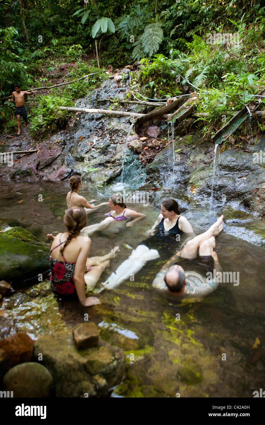 Peru, Cruz de Mayo, Manu National Park, Pantiacolla mountains. Tourists relaxing in stream of hot springs. - Stock Image