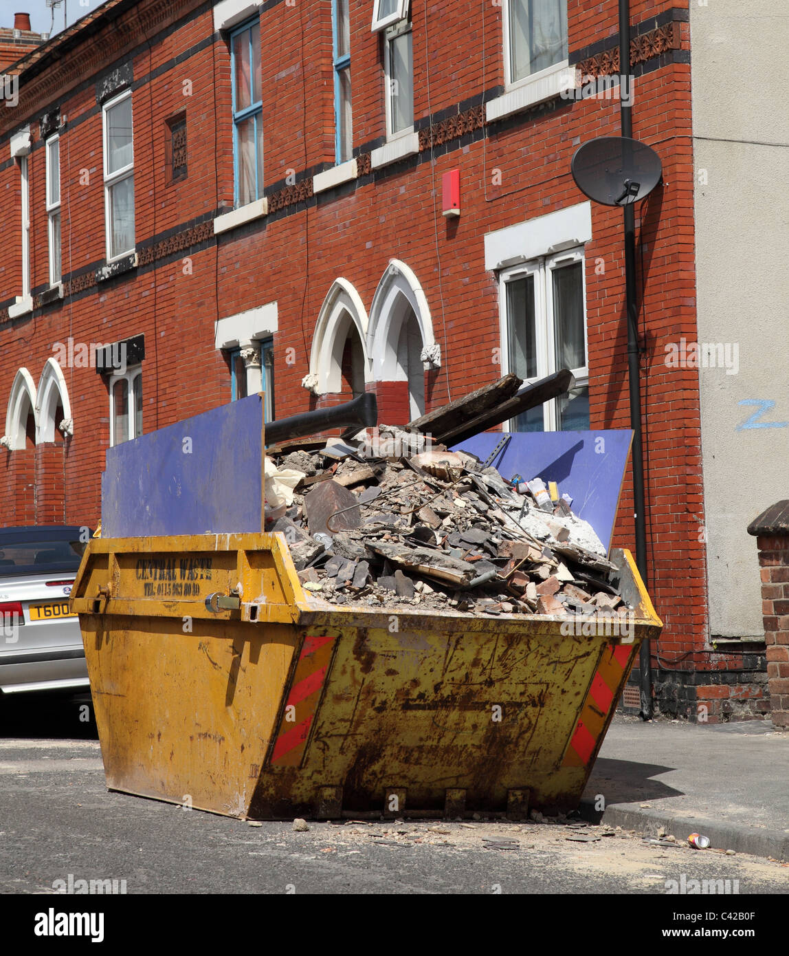 A skip outside a house in a U.K. city. - Stock Image