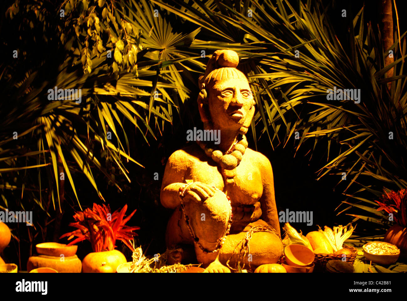 Statue of Ixchel, a Mayan fertility and moon goddess, surrounded by offerings, Xcaret park, Riviera Maya, Quintana - Stock Image