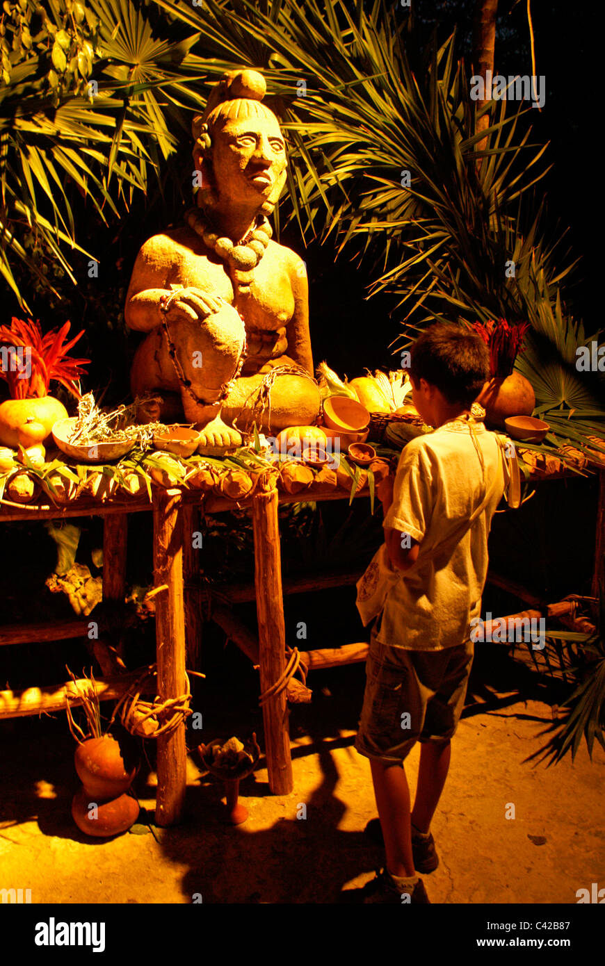 Mexican boy looking at Ssatue of Ixchel, a Mayan fertility and moon goddess, surrounded by offerings, Xcaret park, - Stock Image