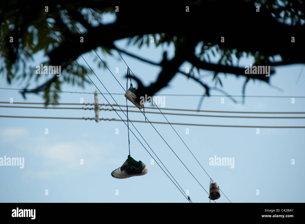 Shoes thrown over wires are a symbol of local gangs - Stock Image