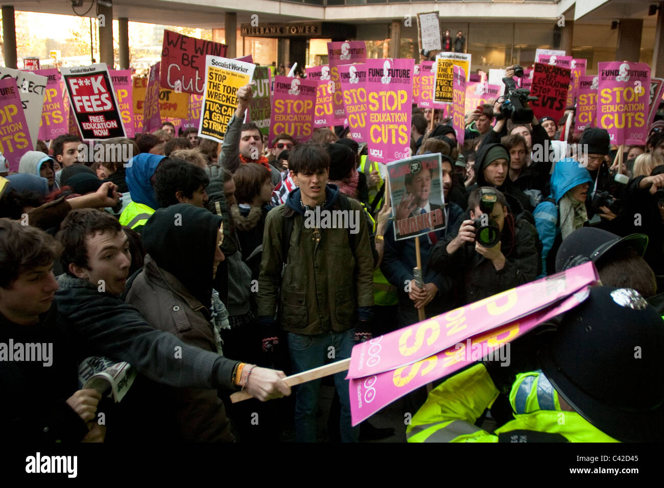 A hits police officers with a placard during the first London student protest in November 2010. - Stock Image