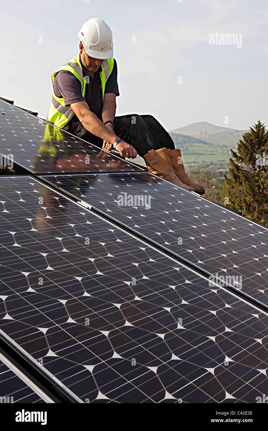 Man fitting solar pv panels to house roof Wales UK - Stock Image