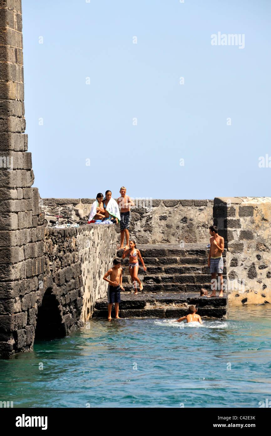 Children jumping into sea from Puente de las Bolas drawbridge to Castle San Gabriel, Arrecife, Lanzarote, 'Canary - Stock Image
