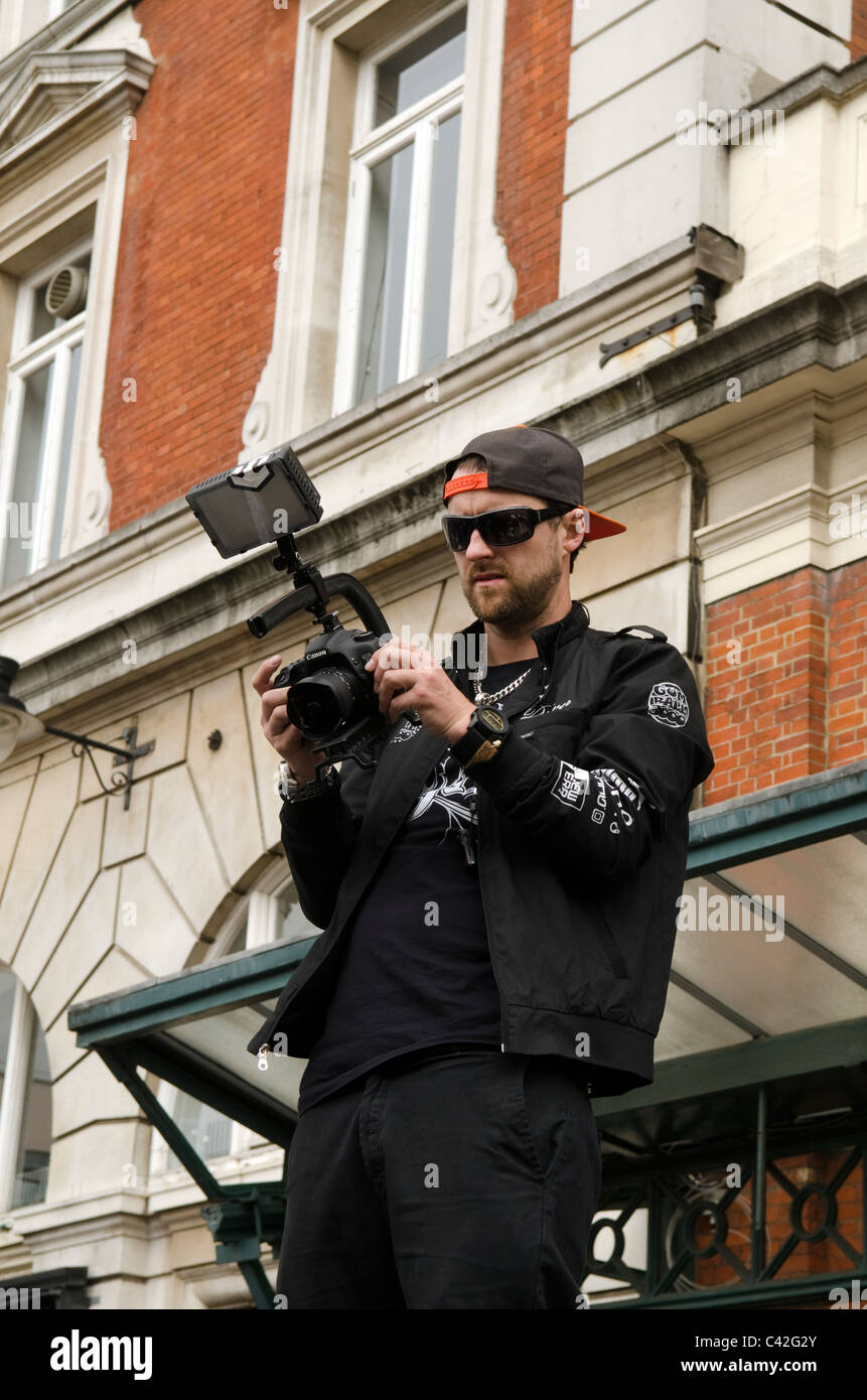 Lee Dainton of SWYD (sleep while you are dead) fame holding a Canon and LED flashgun at the Gumball rally 3000 Covent - Stock Image