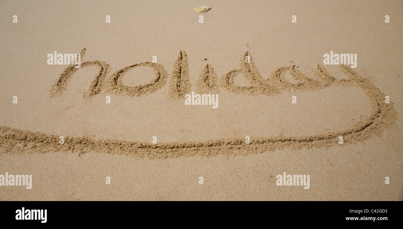 Holiday written in sand - Stock Image