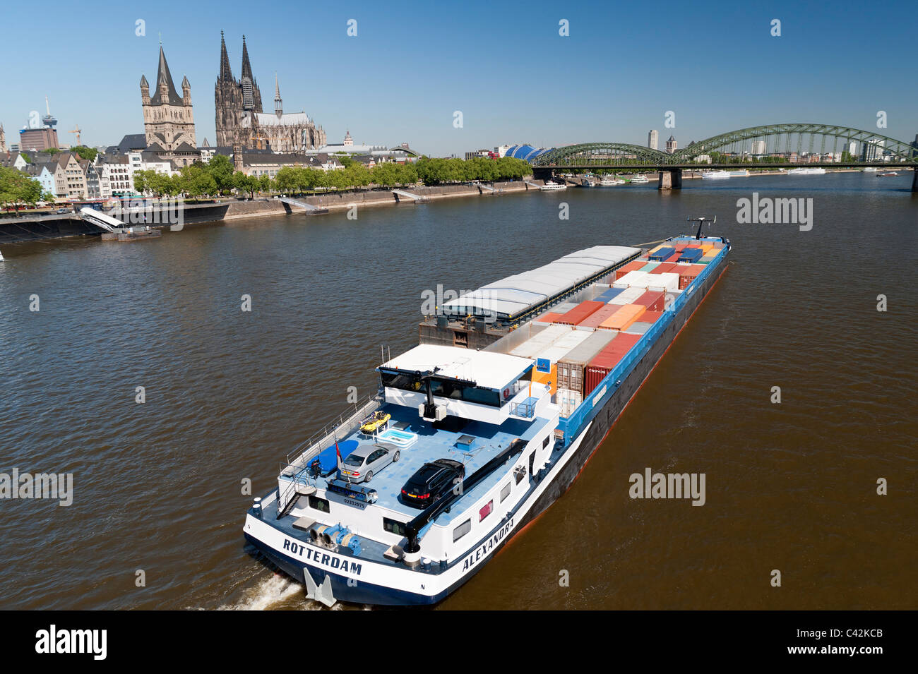 A Barge carrying shipping containers travels along the River Rhine in Cologne Germany - Stock Image