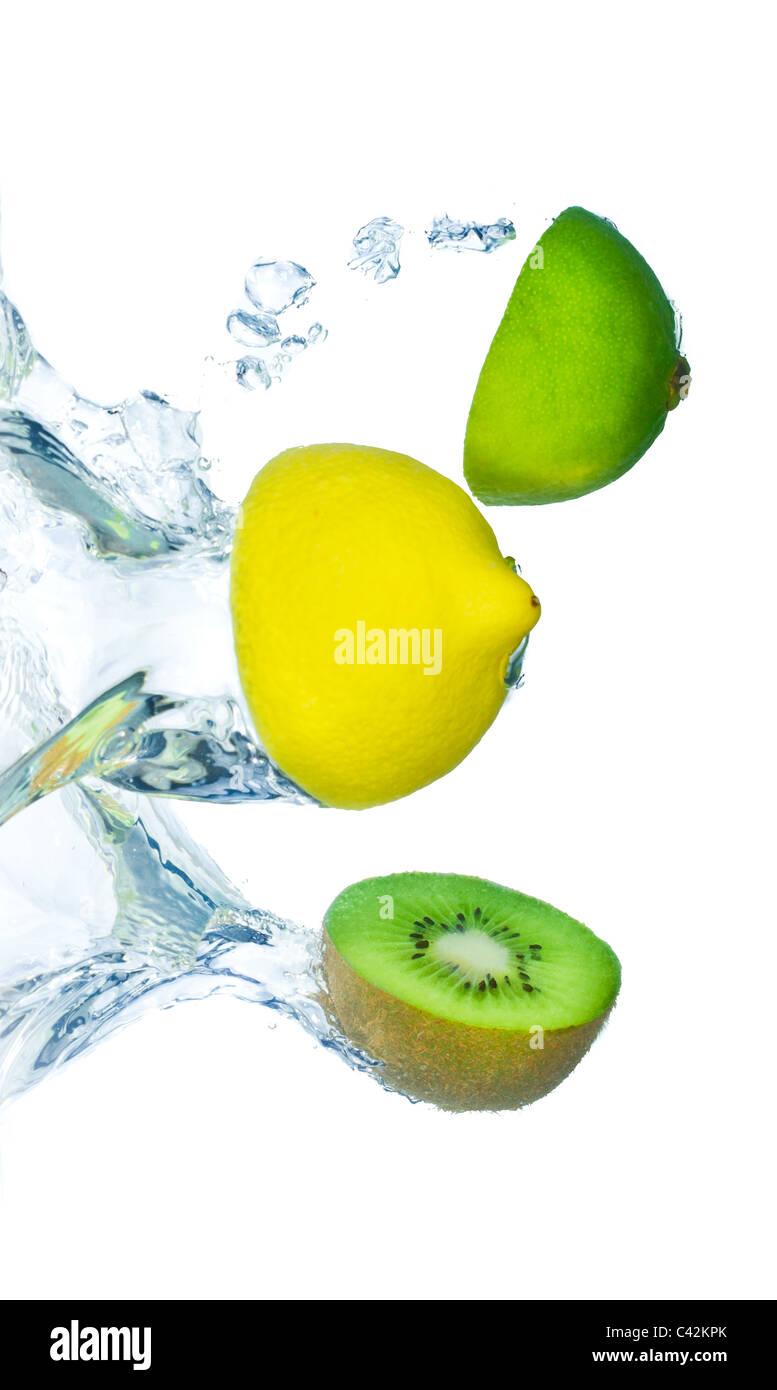 citrus fruit with kiwi splashing on white background - Stock Image