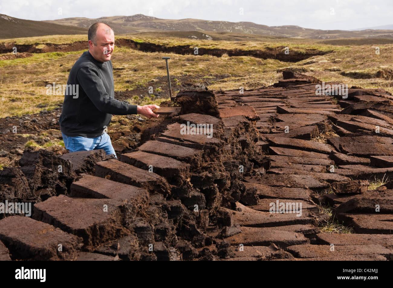 Shetland Islands, Scotland, UK, Europe. Man cutting peat blocks for traditional fuel - Stock Image