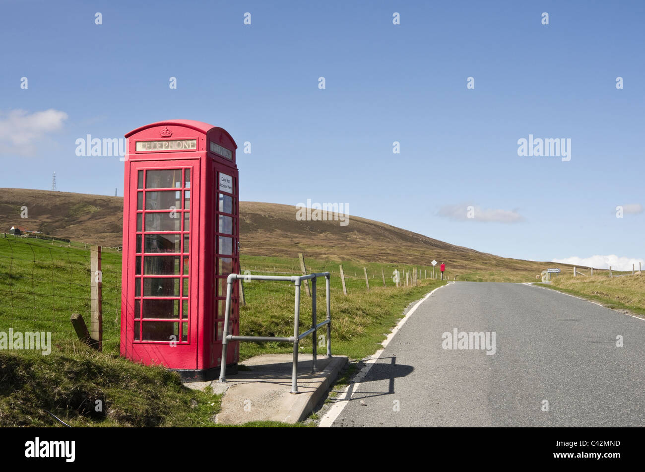 Single track empty country road and red telephone kiosk box. Voe, Northmavine, Shetland Islands, Scotland, UK, Britain. - Stock Image