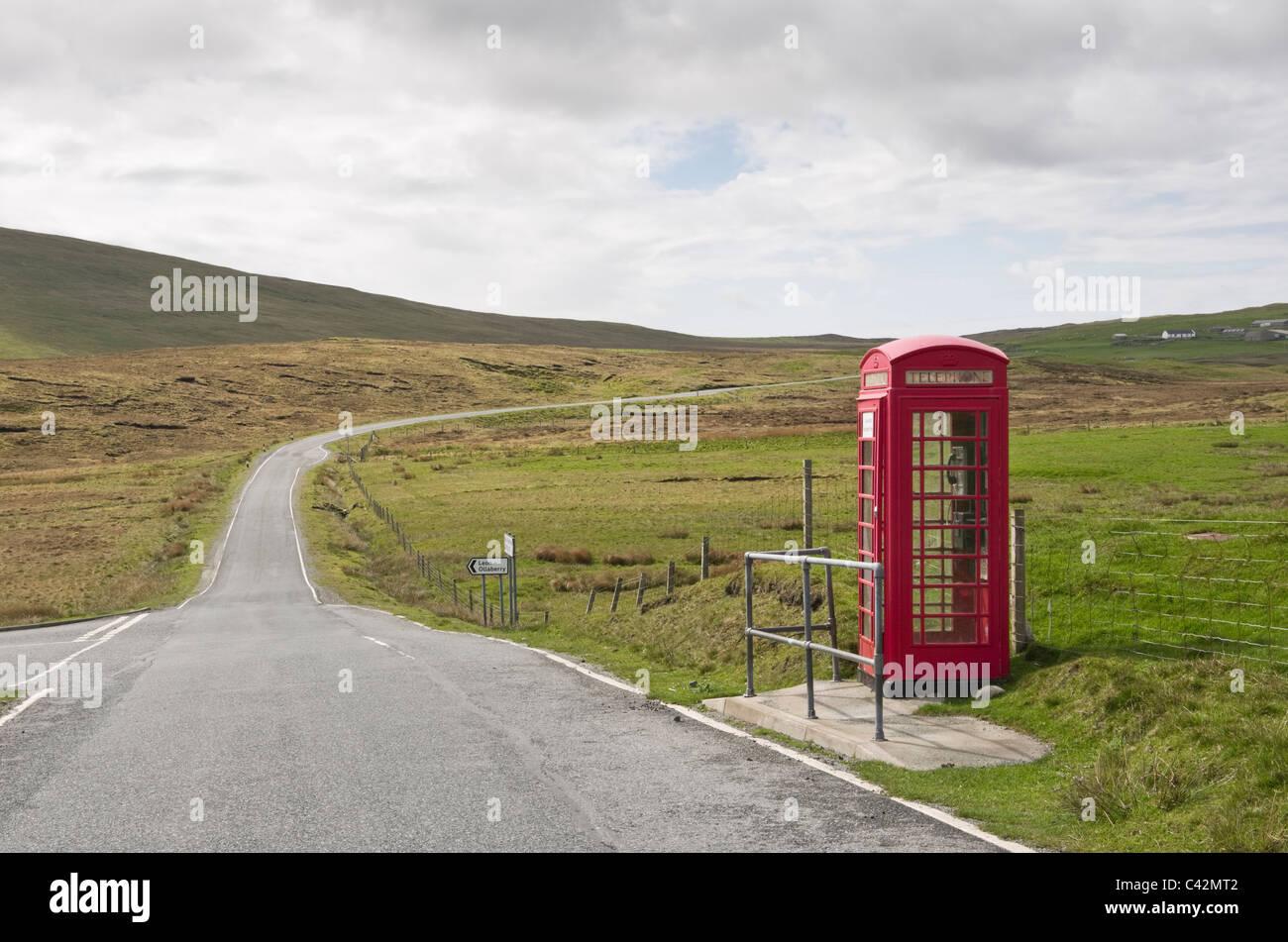 Voe, Northmavine, Shetland Islands, Scotland, UK, Britain. Single track country road and red telephone kiosk. - Stock Image