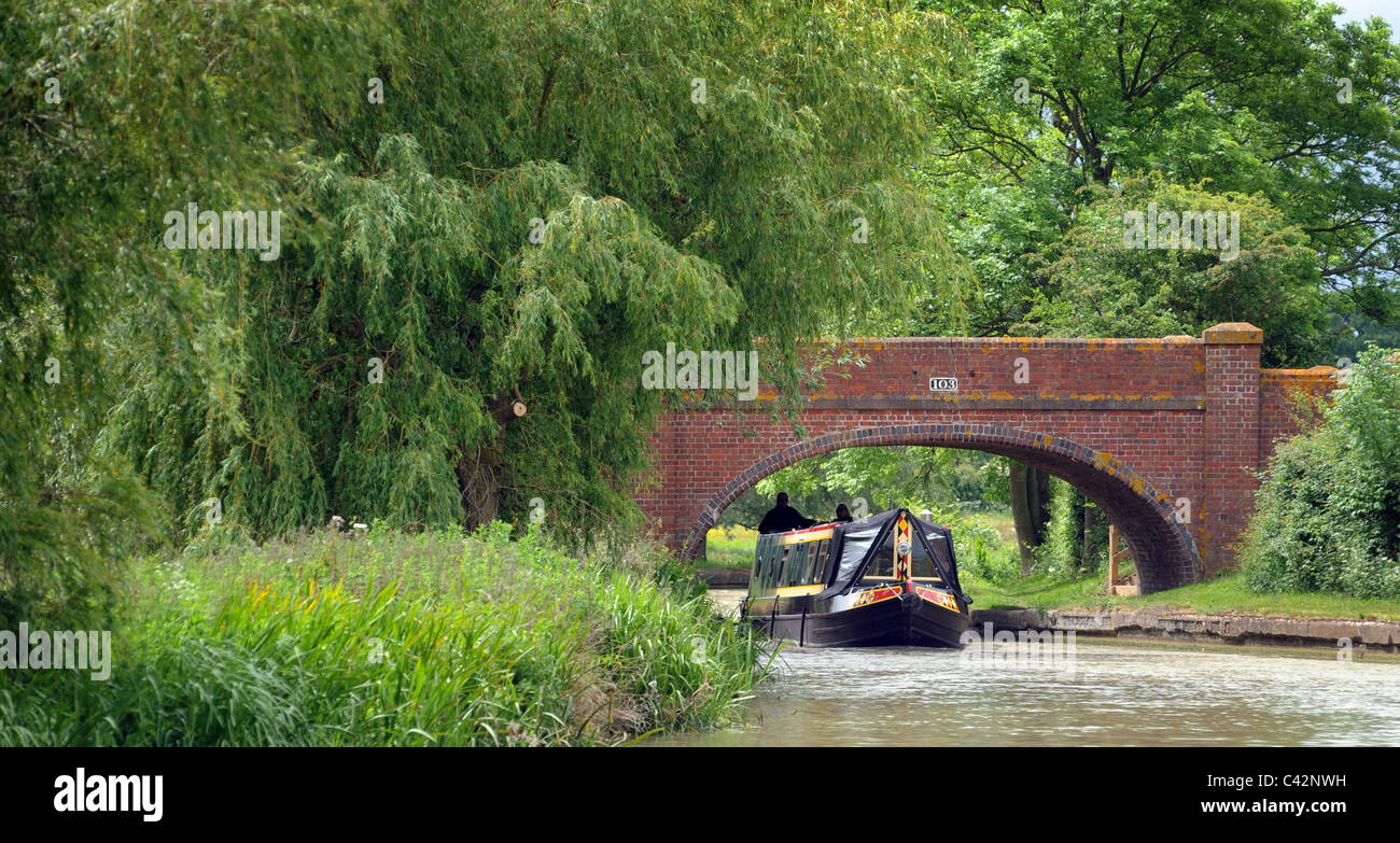 NARROWBOATERS  TRAVELLING UNDER A CANAL BRIDGE ON BARGE RE BRITISH CANAL SYSTEM BOATING HOLIDAYS NARROWBOATS   WATERWAYS - Stock Image