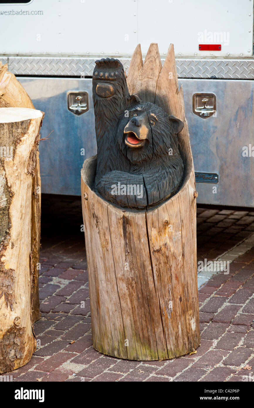 Wood carving of a black bear in a log stump waving - Stock Image