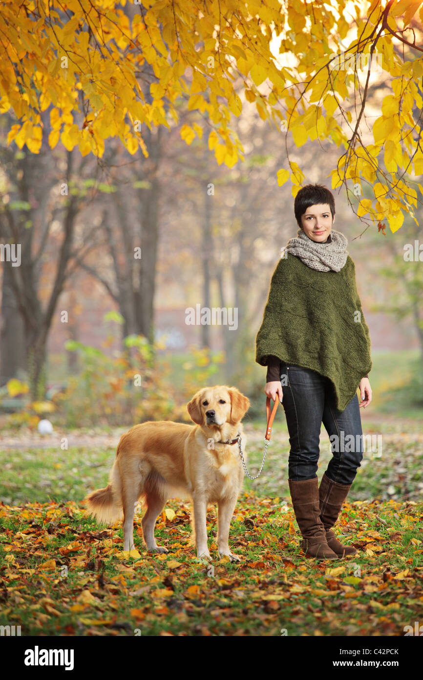 Young girl and her dog (Labrador retriever) walking in autumn in a city park - Stock Image